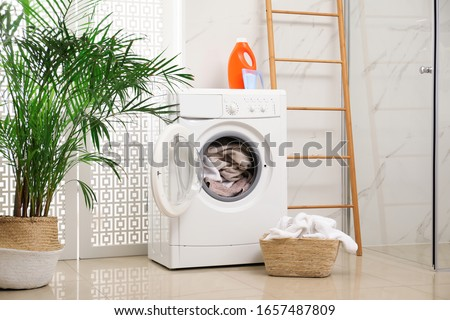 Modern washing machine with towels in bathroom #1657487809
