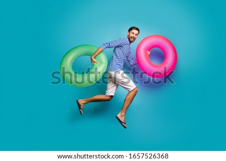Full length photo of funky crazy guy tourist jump high running swimming hold two colorful lifebuoys circles wear striped sailor shirt shorts flip flops isolated blue color background #1657526368