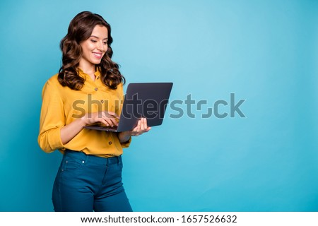 Portrait of her she nice attractive lovely cheerful cheery wavy-haired girl holding in hands laptop creating presentation isolated over bright vivid shine vibrant green blue turquoise color background