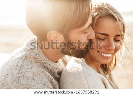 Close up of a smiling beautiful young couple embracing while standing at the beach #1657558291