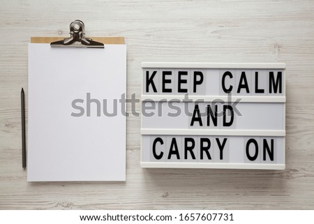 'Keep calm and carry on' words on a modern board, clipboard with blank sheet of paper on a white wooden background, top view. Overhead, from above, flat lay.