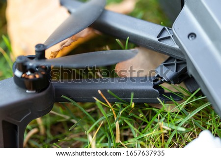 Broken black quadcopter drone uav lying on green grass lawn on ground after crash accident. Remote control failure due to strong wind interference. Cracked camera gimball and plastic legs #1657637935
