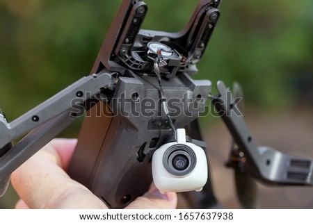 Pilot holding in hand broken black quadcopter drone uav after crash accident outdoors . Remote control failure due to strong wind interference. Cracked camera gimball plastic legs #1657637938