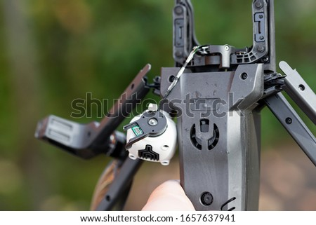Pilot holding in hand broken black quadcopter drone uav after crash accident outdoors . Remote control failure due to strong wind interference. Cracked camera gimball plastic legs #1657637941