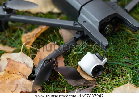 Broken black quadcopter drone uav lying on green grass lawn on ground after crash accident. Remote control failure due to strong wind interference. Cracked camera gimball and plastic legs #1657637947
