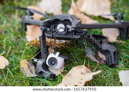 Broken black quadcopter drone uav lying on green grass lawn on ground after crash accident. Remote control failure due to strong wind interference. Cracked camera gimball and plastic legs #1657637950