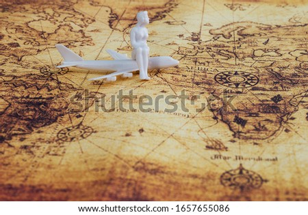 Model plane and figurine on world map background. #1657655086