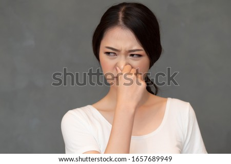 asian woman covering her nose for bad smell, concept of stink thing, bad breath, unpleasant smell, rotten food, odor, body bad smell; young adult Chinese asian woman model #1657689949
