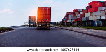 Back view of Red Container truck in ship port Logistics.Transportation industry in port business concept.import,export logistic industrial Transporting Land transport on Port transportation storge   Royalty-Free Stock Photo #1657693114