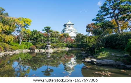 Landscape picture of Osaka castle with reflection on water in seasoning autumn leaves colorful garden around castle