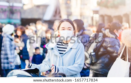 Coronavirus Covid19 virus and pm2.5 concept.Japanese mother with kids wearing mask for protect pm2.5 and Covid-19 virus outdoor at Tokyo.Social distancing coronavirus and pandemic virus symptoms. #1657717834