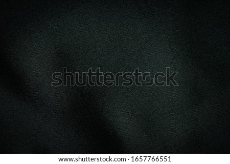 Black fabric, luxury dark gray background abstract. Material are used in textile assembly. Detail cloth texture of pattern. Design, elegance with vignette effect, free copy space for text placement.