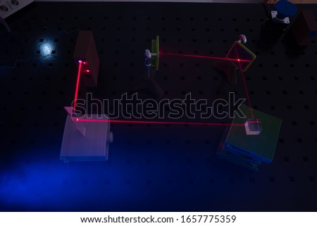 Experiment in optic lab with laser device. Red laser on optical table in physics laboratory #1657775359
