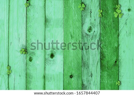 St Patricks Day topview border of leaves shamrocks on Vintage green vertical wood planks.