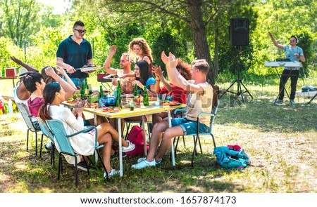 Happy friends having fun together at barbeque pic nic party - Multiracial young people at open air food festival - Youth friendship concept with guys and girls eating at garden barbecue - Warm filter