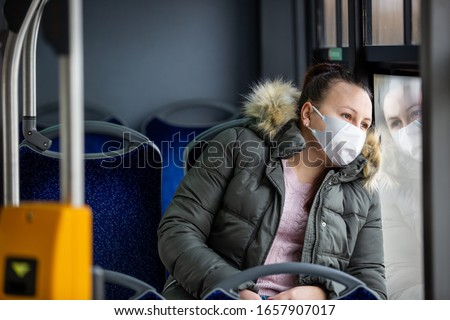 Coronavirus, covid 2019, young woman with respiratory mask traveling in the public transport by bus #1657907017