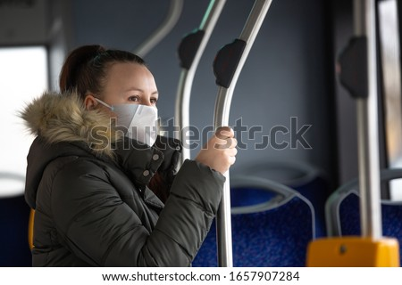 Coronavirus, covid 2019, young woman with respiratory mask traveling in the public transport by bus #1657907284