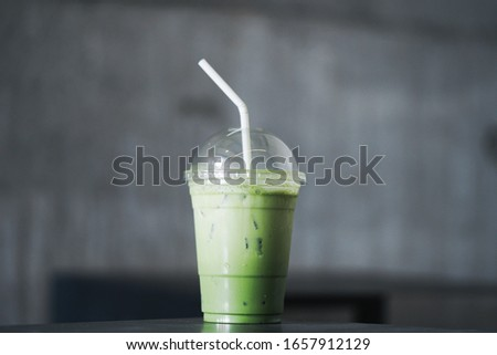Japanese Matcha green tea ice latte on table.Iced mocha or matcha green tea latte in takeaway cup in cafe restaurant.Drinking Menu picture.