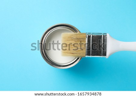 Paint can and brush on blue background, top view #1657934878