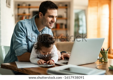 Young happy father reading e-mail on a computer while being with his baby daughter at home.  #1657938091