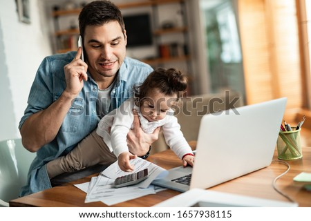 Young working father talking on the phone while babysitting his playful daughter at home. Royalty-Free Stock Photo #1657938115