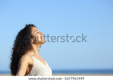 Side view portrait of a relaxed young woman breating and enjoying sun on the beach in summer Royalty-Free Stock Photo #1657961449