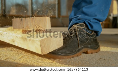 CLOSE UP, DOF: Detailed shot of a painful work accident as a heavy plank falls on an unrecognizable worker's foot. Worker sawing wood drops a beam on his foot. Unlucky construction site accident Royalty-Free Stock Photo #1657964113
