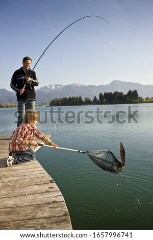 Father and son fishing in lake #1657996741