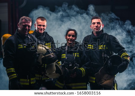 Group picture of firefighters with fire extinguisher's smoke in the background