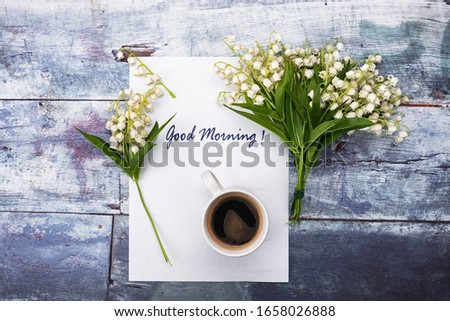 A white cup with coffee, a lily of the valley bouquet and a good morning card arranged on a vintage purple surface