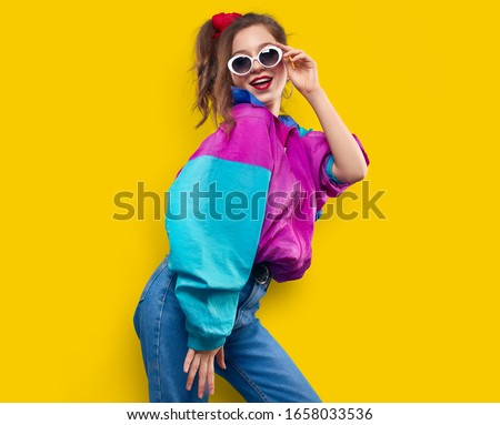 Cool teenager. Fashionable DJ girl in colorful trendy jacket and vintage retro sunglasses enjoys style of 80s - 90s vibes. Teenager Girl at disco party. Young fashion model on yellow color background. #1658033536