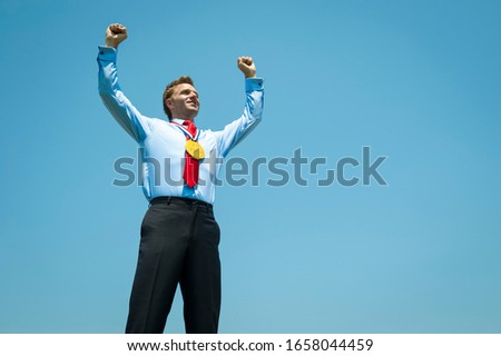 Gold medal businessman pumping his fists in the air against blue sky #1658044459