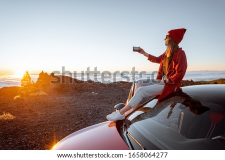Young woman dressed in red enjoying sunset landscape above the clouds, sitting on the car roof while travel in the mountains. Carefree lifestyle and travel concept