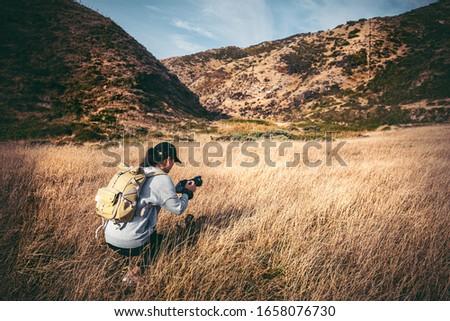 Female photographer hiking on Makara hill, Wellington, NZ
