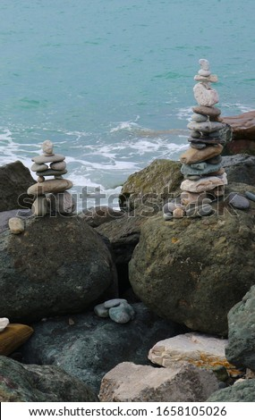 Stone cairn on seacoast. Big rocks and balanced pebbles stack. Relaxation, harmony, balance concept.           #1658105026