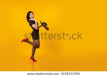 Young brunette woman in a short black dress holds a black hat with large brim and poses on a yellow background #1658155396