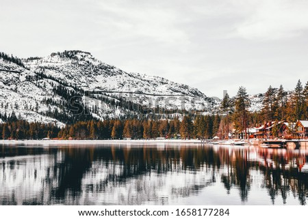 Wooden Houses and pine trees at the donor lake with the huge snowy mountains in the background at the donner lake tahoe national forest california