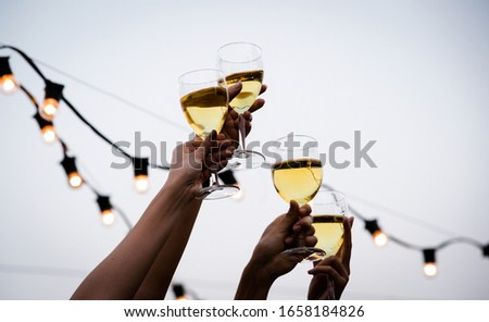 Cheers! Group of people cheering with champagne flutes with party background, Concept Celebration. #1658184826