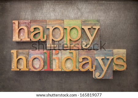 happy holidays - text in letterpress wood type against grunge metal background