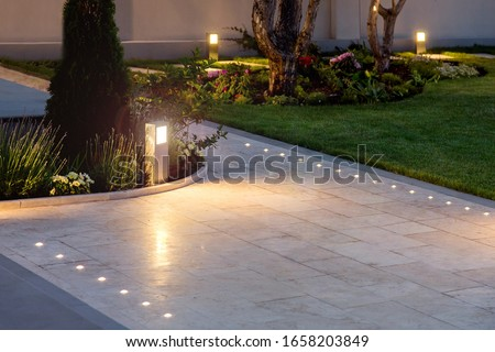 marble tile playground in the night backyard of mansion with flowerbeds and lawn with ground lamp and lighting in the warm light at dusk in the evening. Royalty-Free Stock Photo #1658203849