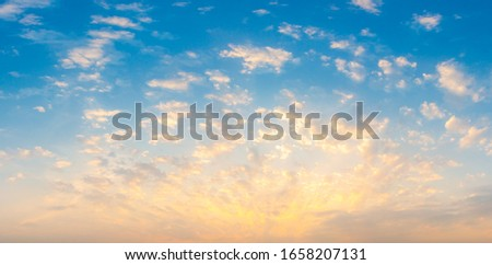 Beautiful Vivid sky painted by the sun leaving bright golden shades.Dense clouds in twilight sky in winter evening.Image of cloud sky on evening time.Evening Vivid  sky with clouds.  Royalty-Free Stock Photo #1658207131