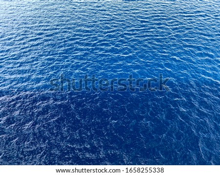 Sea background. Close-up texture of blue water. Ripple of blue sea water. Textured ocean water background. Cropped shot, horizontal, free space. Rest and travel concept.