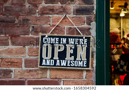 """Come in we're open and awesome."" A playful sign invites customers into a store."