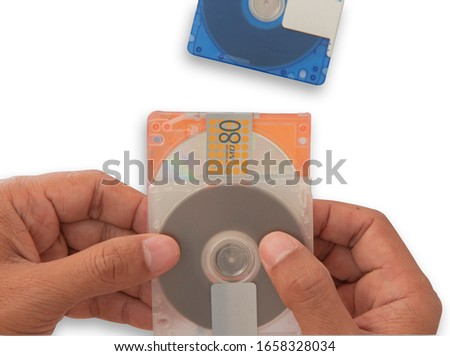 Isolate mini disc MD in hand. Put on white background for data and music recording, Concept music players, high-capacity music discs, old rewritable data sheets  with clipping parts.