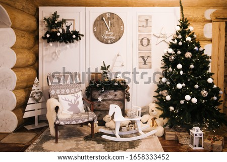 Christmas decorations: chair, Christmas tree, chest of drawers, clock, gifts on the background of a wooden wall. Christmas Photo Zone. Christmas photo zone