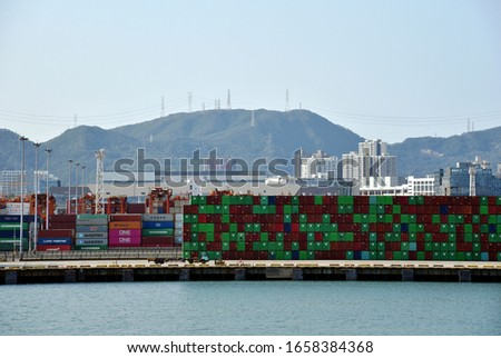 Yantian / China - February 21 2020: View of the sea port and container terminal in Yantian. Containers stored on the berth, waiting to be loaded on arriving cargo ship. #1658384368