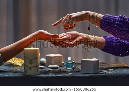 Magic gypsy woman reading palm lines around candles and other magical accessories. Witch during fortune telling palmistry, prediction the future life and divination ritual  Royalty-Free Stock Photo #1658386255