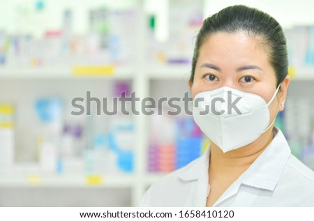 Portrait of young female doctor wear N95 mask on many medicine shelf background. Coronavirus (COVID-19)concept of disease, flu treatment and protection. Royalty-Free Stock Photo #1658410120