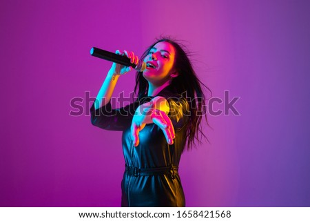 Caucasian female singer portrait isolated on purple studio background in neon light. Beautiful female model in black wear with microphone. Concept of human emotions, facial expression, ad, music, art. #1658421568