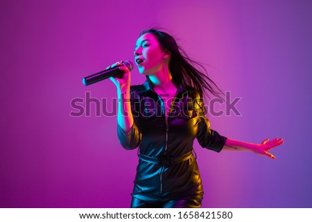 Caucasian female singer portrait isolated on purple studio background in neon light. Beautiful female model in black wear with microphone. Concept of human emotions, facial expression, ad, music, art. #1658421580